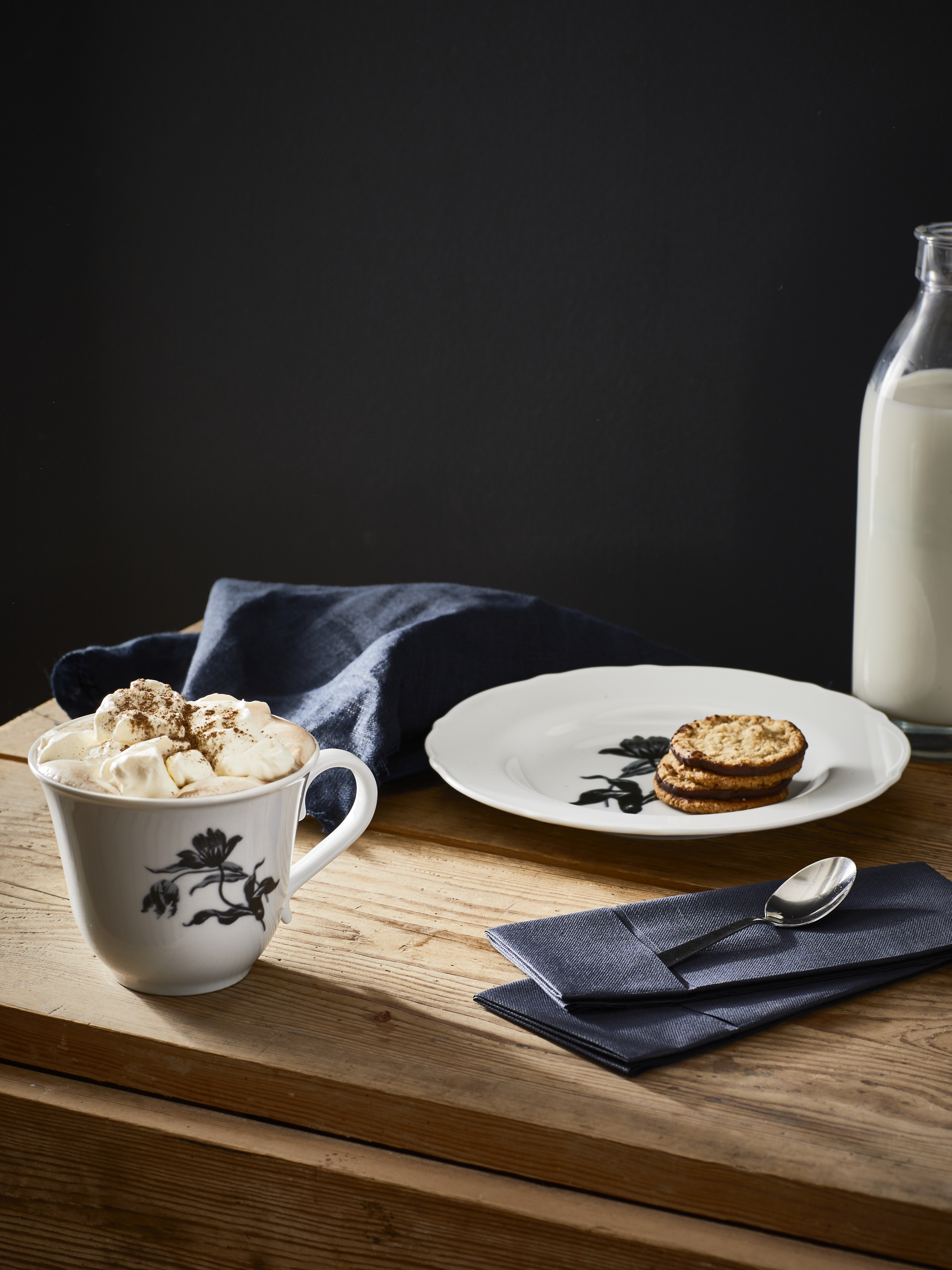 A wood table top with a plate of cookies, a jar of milk and a cup of hot cocoa sitting with black napkins and cutlery.