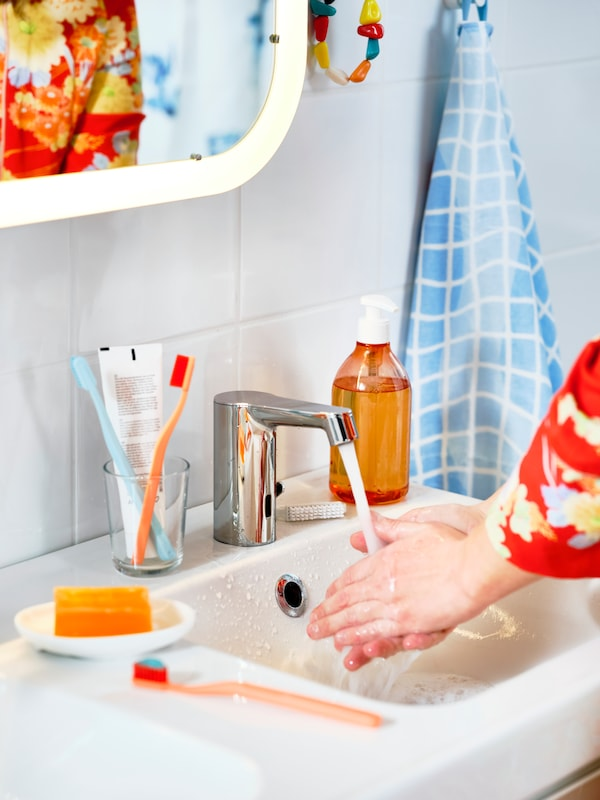 A woman washes her hands under a BROGRUND faucet with sensor next to toothbrushes, soap and a blue/ white towel.