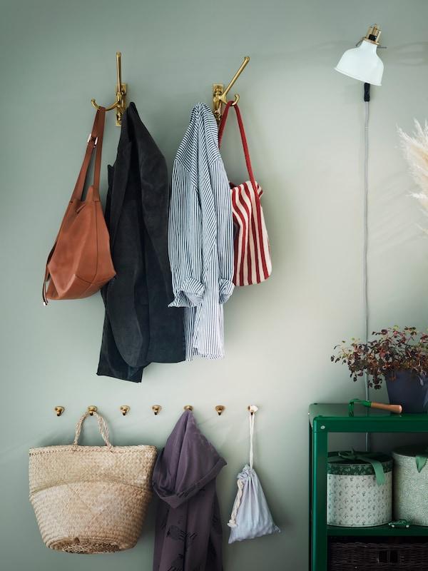 Dous ganchos xiratorios triplos KÄMPIG con roupa colgada montados nunha parede, enriba duns ganchos KVASP.