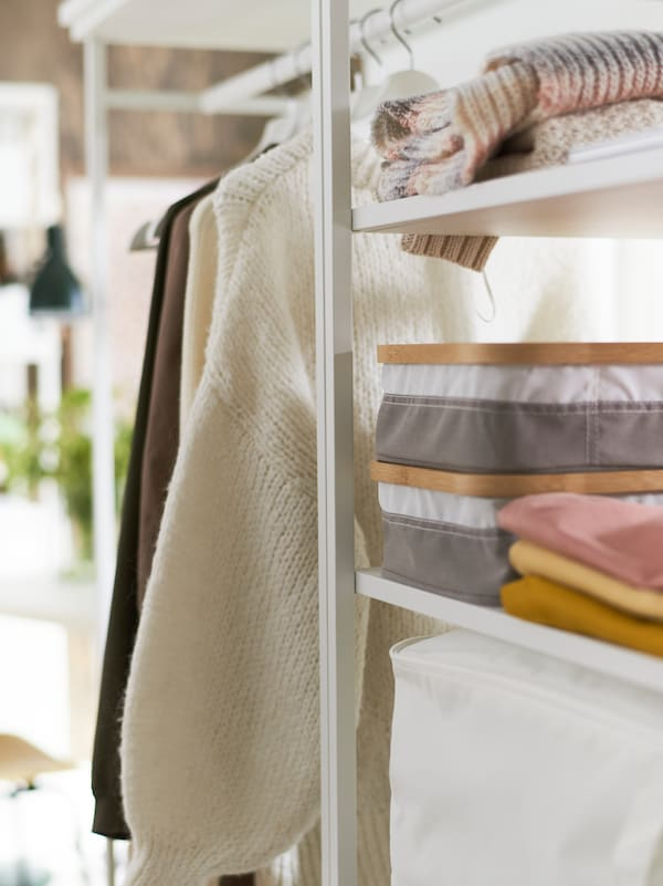 Part of a white PLATSA open shelving unit with boxes and clothes on shelves and more clothes hanging from a rail.