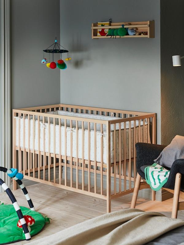 Lit à barreaux SNIGULAR dans une chambre de bébé. Il y a une chaise dans le coin de la pièce. Un mobile est suspendu au-dessus du lit à barreaux.
