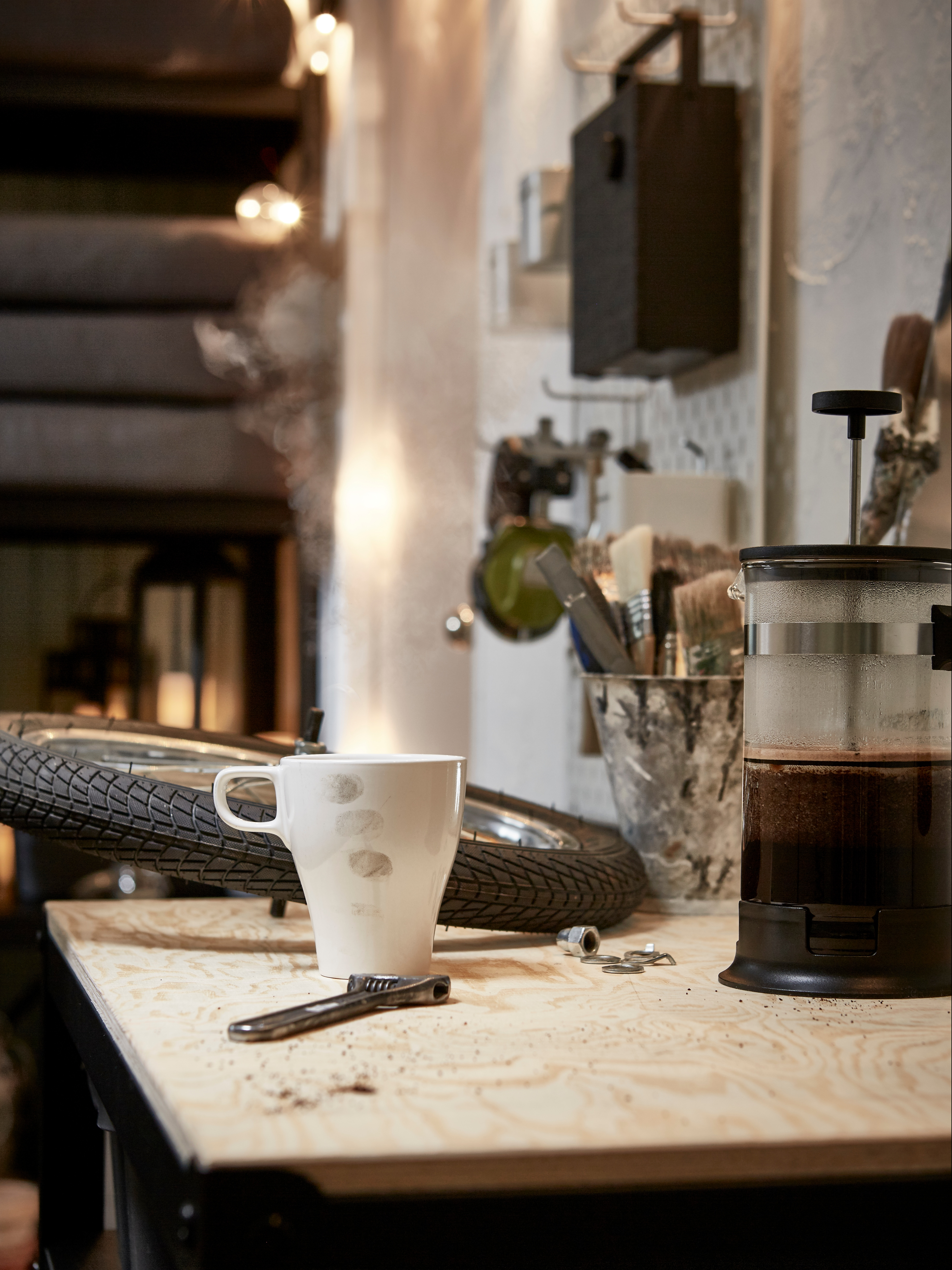 A worktop in a garage room that has a bike wheel, a wrench, a white FÄRGRIK stoneware mug and a steamy, glass coffee maker.