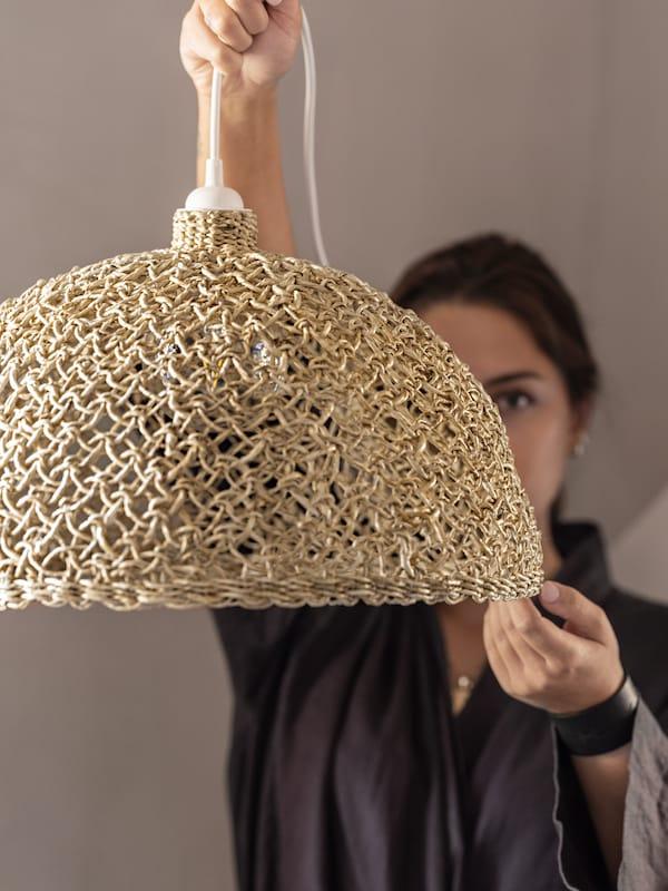 女性がLOKALT/ロカルト ランプシェードを持ち上げている。ランプシェードは、インドの熟練した職人がバナナ繊維を使って手編みしている。