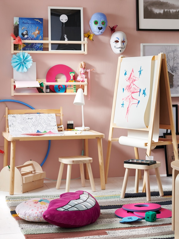 A child's room with a MÅLA easel and FLISAT children's stools and table. There are paintings and other artworks on the wall.