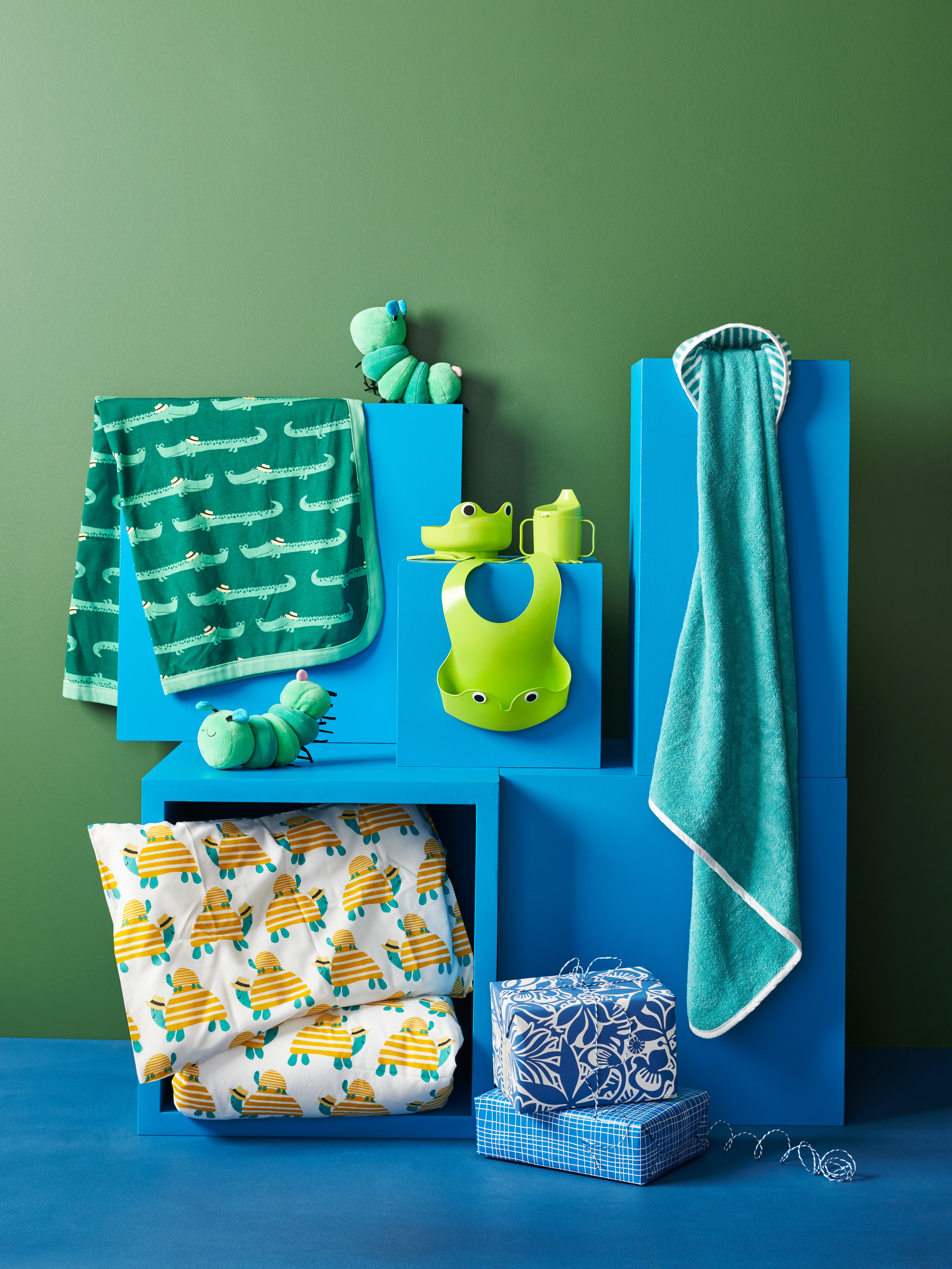 Children's bed linen, towels, soft toys and cup, bowl and bib set arranged on a blue shelving unit with wrapped presents.
