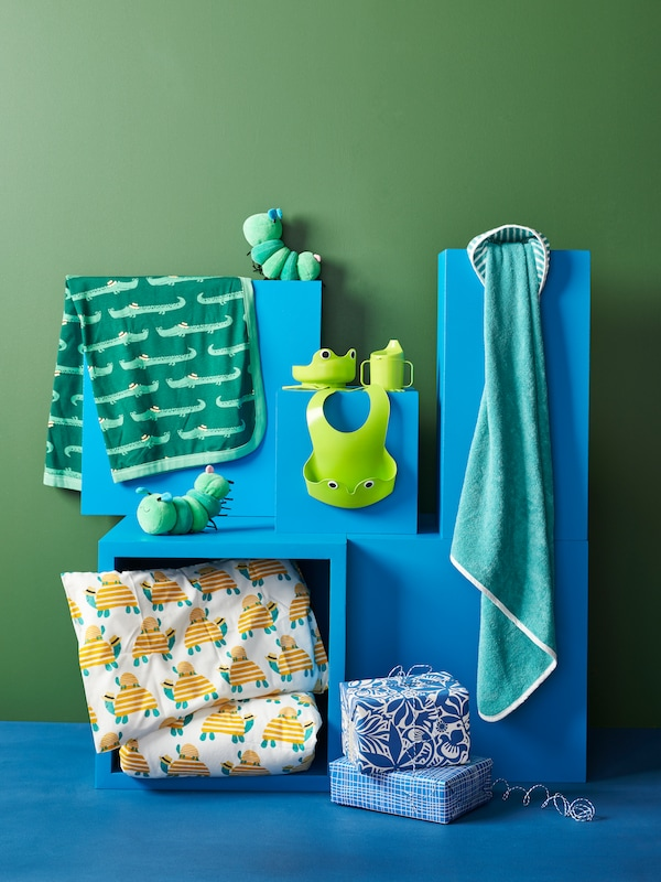 Several baby items in blue and green including towels, bed linen, a bib, and a toy.