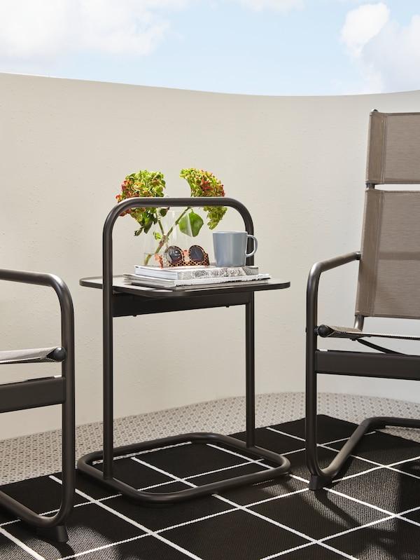 طاولةجانبيةرماديداكنبيد على سجادةبين كرسيين بذراعين. نظارة شمسيةوكوبأعلىالطاولة.