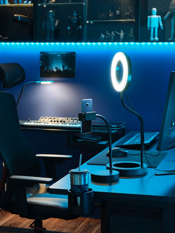 Blue LED strip lights dimly lighting corner desk space. Ring light extended, cup holder attached to end of desk.