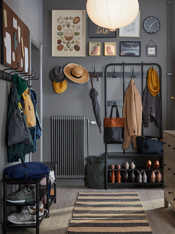 A grey-painted hallway with PINNIG coat rack, bench and row of hooks, holding clothes and shoes, and a rug on the floor.