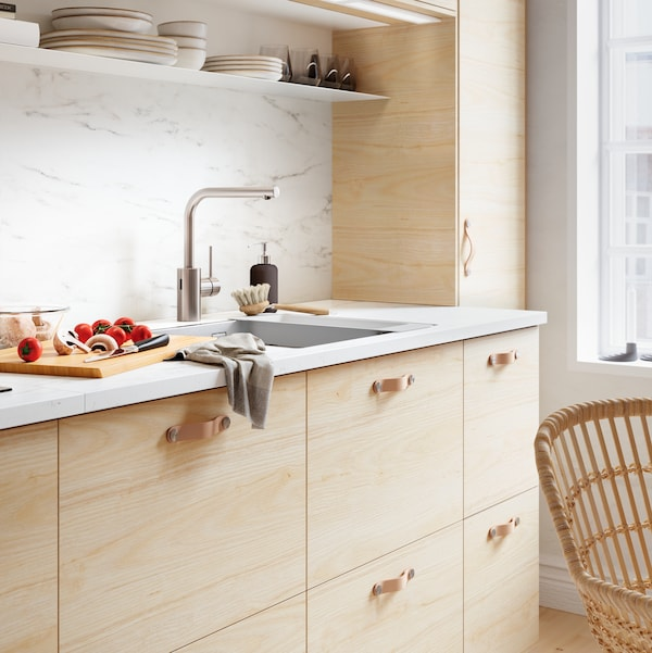 A METOD/ASKERSUND kitchen with wooden fronts, leather handles, white worktop and white marbled splashbacks.