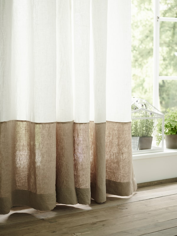 A long curtain, made by sewing a wide strip of AINA natural color fabric onto a white AINA curtain, hangs in a window.