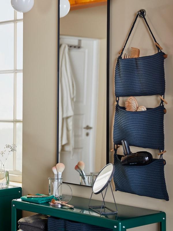 Un espace beauté dans une salle de bains comprenant un rangement suspendu NORDRANA, un miroir mural et une étagère verte.