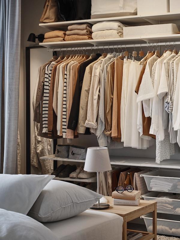 Une armoire-penderie ouverte BOAXEL avec des vêtements suspendus sur une tringle à vêtements. Plus de vêtements et de chaussures se trouvent sur les tablettes et dans les paniers.