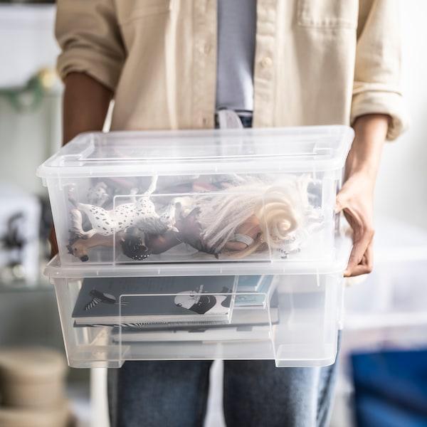 une femme tenant des caisses de rangement en plastique