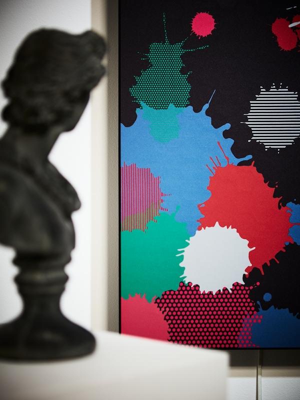 Gros plan d'un cache-enceinte SYMFONISK pour cadre avec enceinte arborant un motif de taches de peinture; buste flou au premier plan.