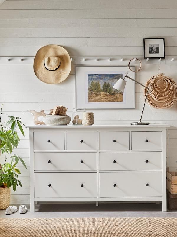 Une commode HEMNES blanche est posée juste à côté d'un mur en planches blanches. Au-dessus d'elle se trouve une tringle avec des crochets, où sont accrochés un chapeau et quelques autres accessoires.