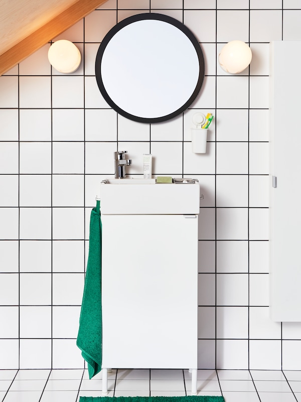 A white small-space bathroom with a black round mirror.