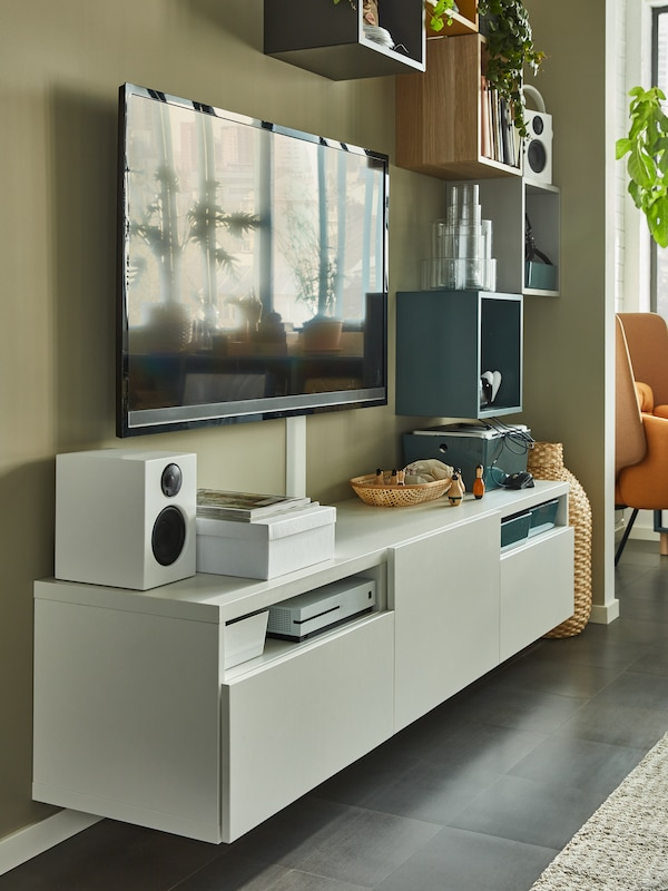 A black TV on a moss green wall. A white TV bench hangs below with a white speaker, consoles, boxes and decoration.