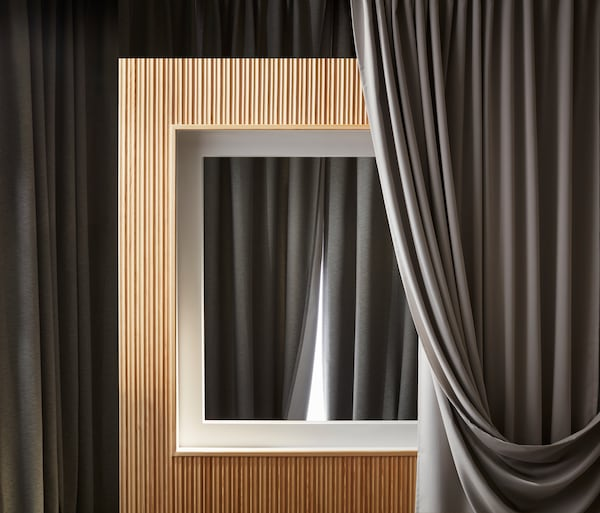 A pair of pink HILJA curtains hang in a window, blowing in the wind. They are open and let sunlight into a white room.