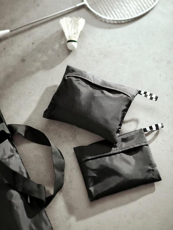Primer plano de dos bolsas RÄCKLA en distintos tamaños, guardadas en bolsas de transporte más pequeñas para una mayor comodidad.