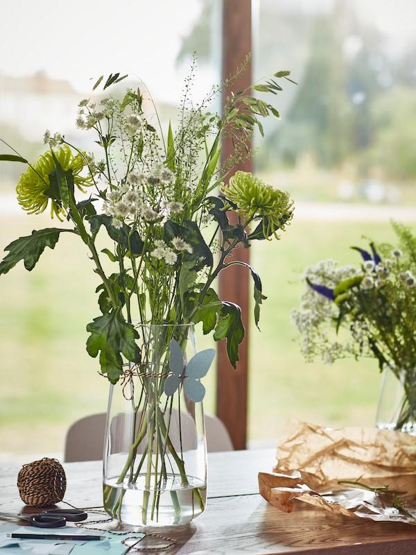 BERÄKNA vase med blomster står på et bord ved et vindu. På bordet er det også hyssing, papir og en penn.
