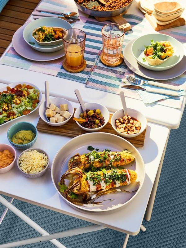 Des aliments grillés, des brochettes, des dips et des sauces sont placés à côté d'assiettes colorées et de verres à boire sur une table extérieure.