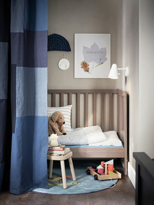 A children's stool and a GULLIVER crib with one side removed and GULSPARV bed linen stand in a corner partly behind a curtain.