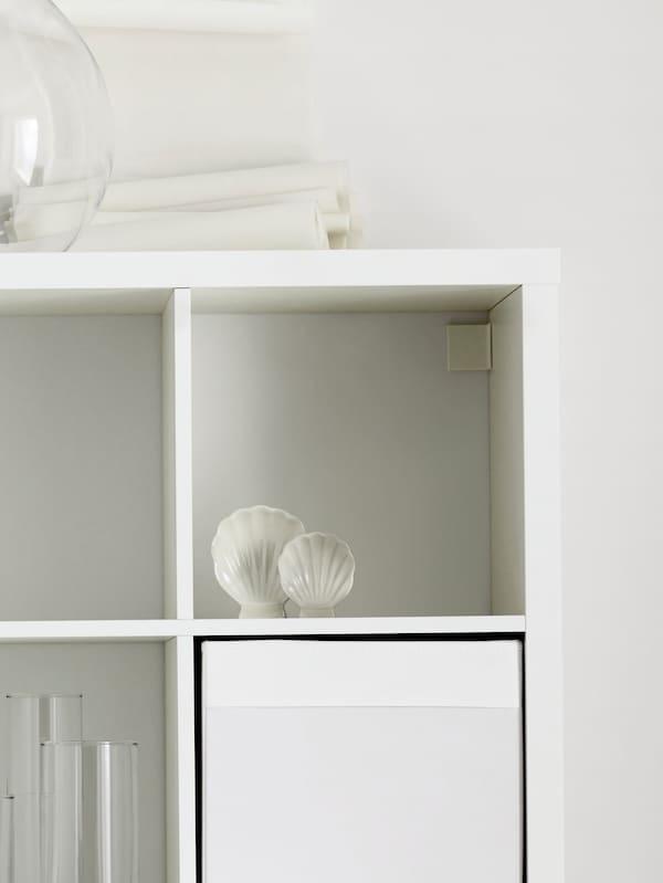 Zgornja desna polica belega KALLAX regala z veliko vazo na vrhu in belimi školjkami na polici.