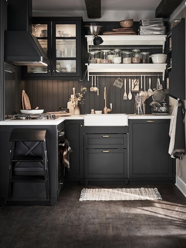 Mala crno bajcana LERHYTTAN kuhinja s bijelim radnim pločama i policama te kuhinjskim priborom koji visi sa šipke.