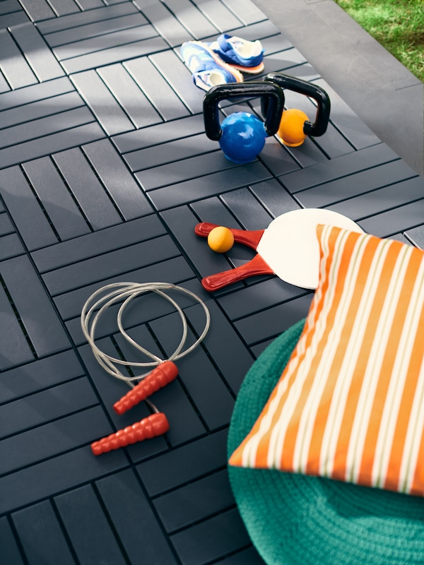 A cushion, a pouffe, weights, shoes, beach ball rackets and a LUSTIGT skipping rope lying on an outdoor RUNNEN floor decking.