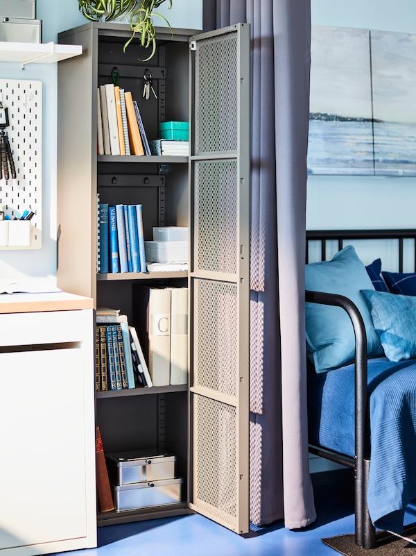 Un dulap IVAR gri cu o ușă de plasă deschisă între un birou alb și un pat de zi negru. Cărți pe rafturi.