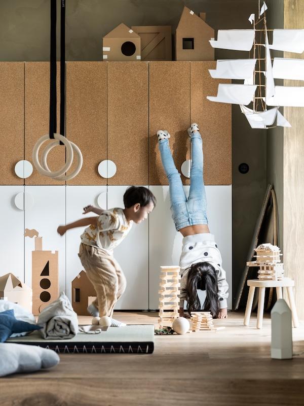 To børn leger foran SMÅSTAD opbevaringssystem, der øverst har låger af kork og nederst hvide låger