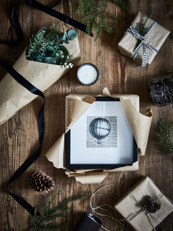 A wooden surface with a black SANNAHED frame mid-unboxing amid a BEHJÄRTAD scented candle, decorations and wrapped gifts.