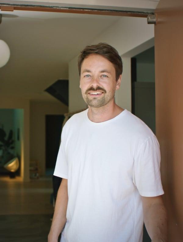 Egy barna hajú férfi fehér pólóban egy ház bejárati ajtajában áll.