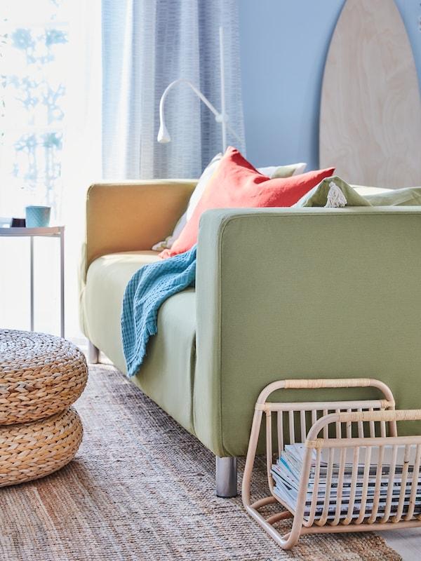 Un canapé klippan vert avec un coussin rouge et un plaid bleu, avec un porte-revues BUSKBO rempli de magazines