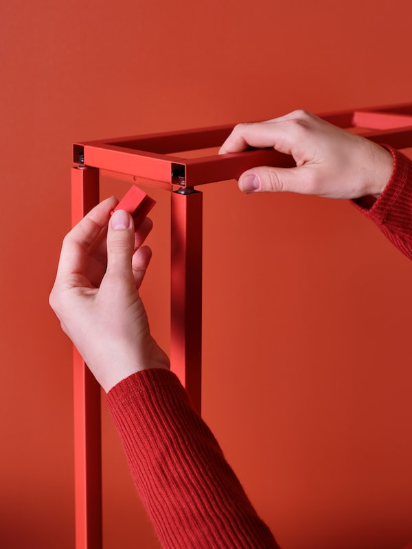 A close up of a hand attaching a dowel inside red ENHET metal frames, against a red background.