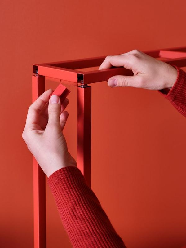 Primo piano di una mano che fissa un tassello all'interno di strutture in metallo ENHET rosse, su sfondo rosso.