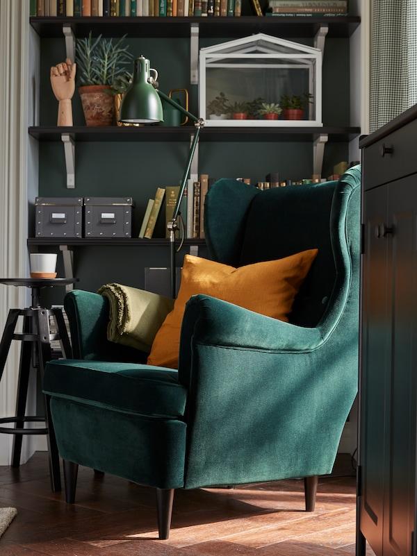 Un sillón orejero STRANDMON en verde oscuro con un cojín encima; está al lado de una lámpara y unos estantes con libros, cajas y plantas.