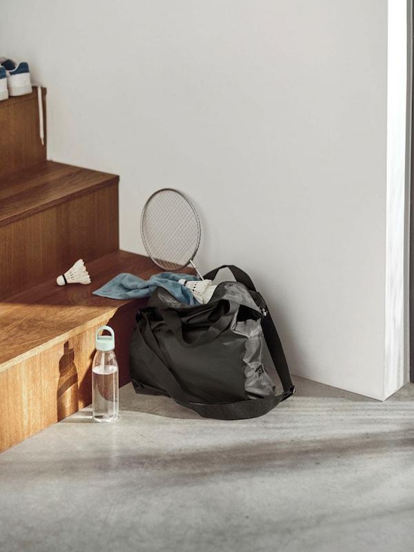 Bolsa RÄCKLA llena de cosas para jugar al bádminton en la parte inferior de una escalera.