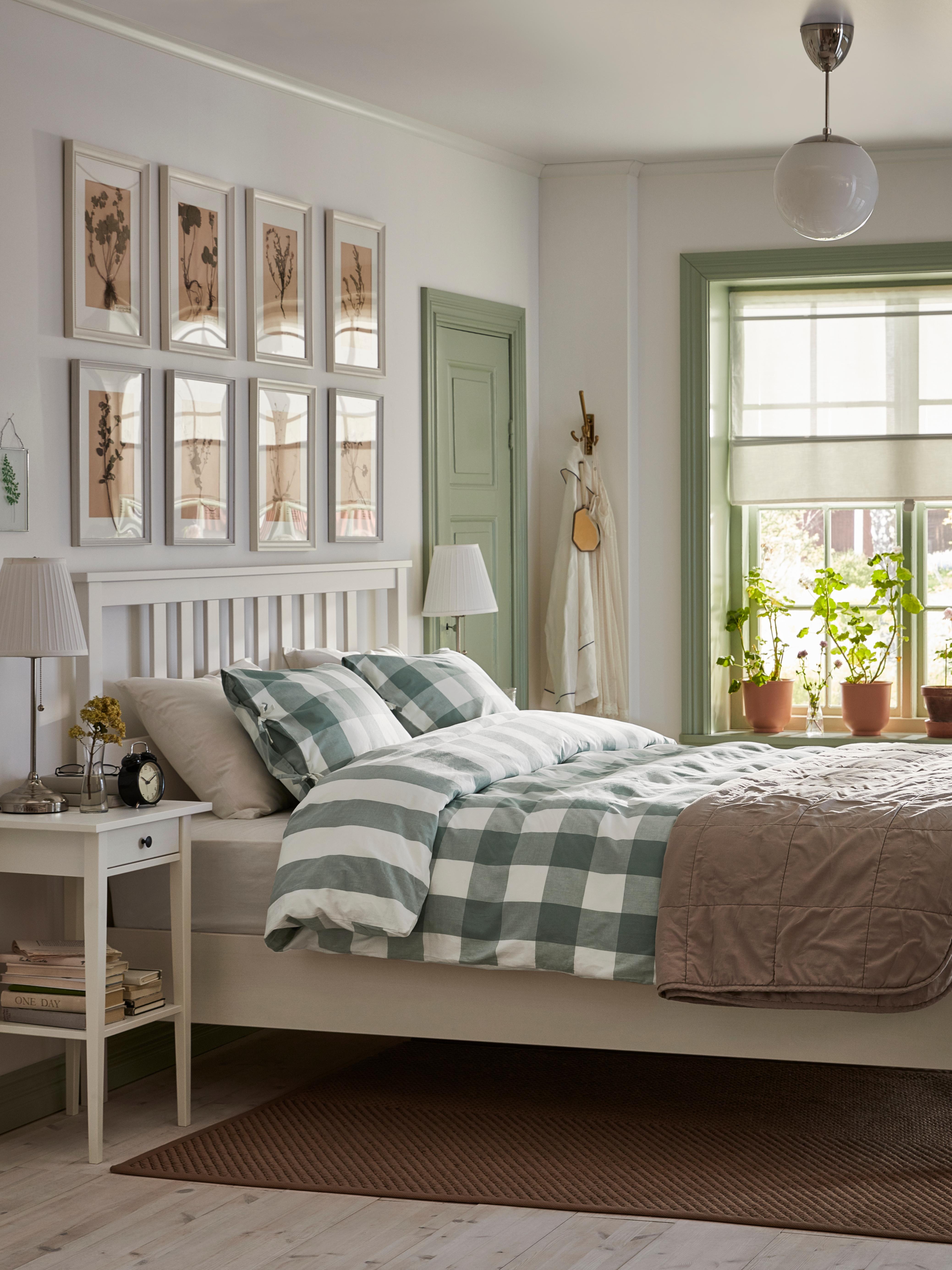 Svijetla spavaća soba s bijelim okvirom kreveta od punog drva bora i zelenom/bijelom navlakom za poplun pokraj noćnih ormarića.