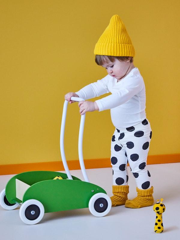 Egy sárga sapkát és fekete-fehér pöttyös nadrágot viselő gyermek egy zöld MULA tipegő teherautót tol egy puha játék mellett.