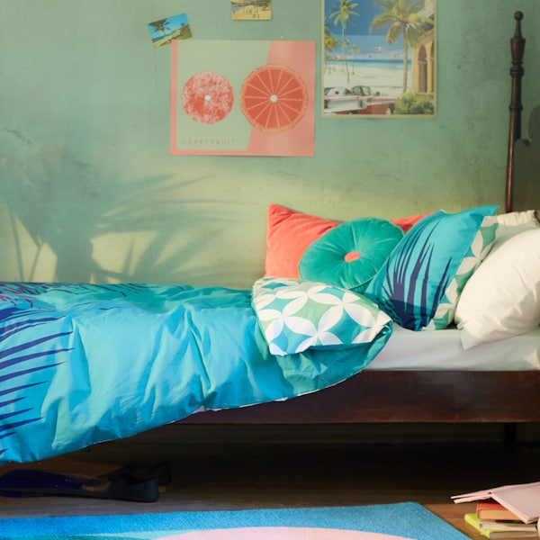 Krevet s GRACIÖS posteljinom s uzorkom pločica i GRACIÖS ukrasnim jastukom na njemu u dječjoj spavaćoj sobi.