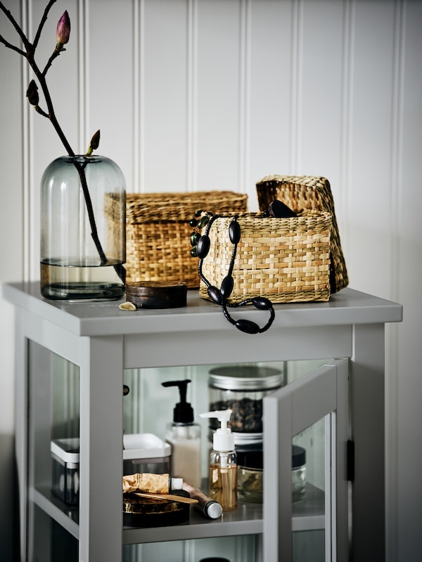 Two LURPASSA seagrass boxes with lids with a black beaded necklace in one of them, above a grey high cabinet with glass door.
