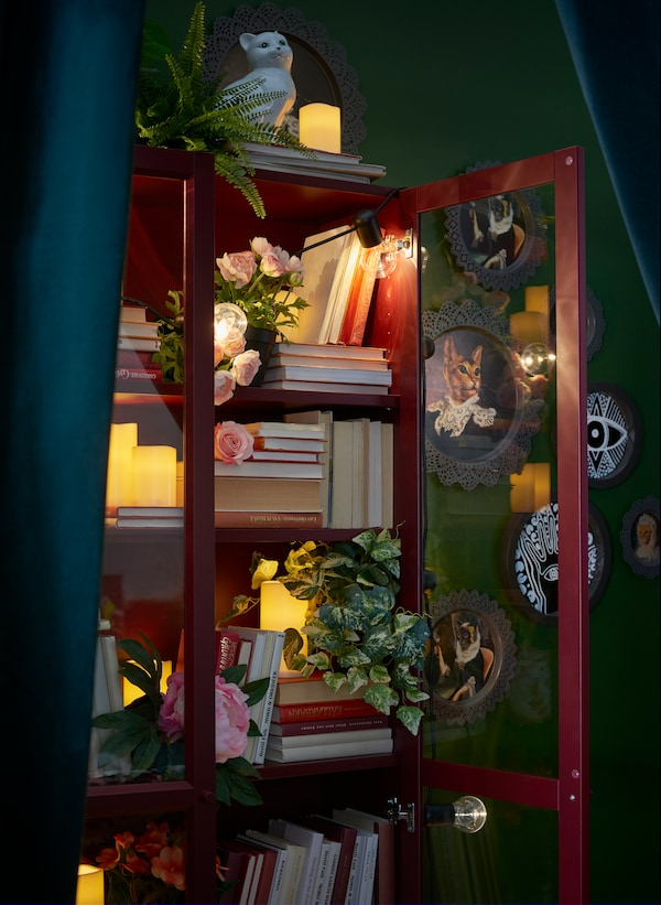 A red BILLY bookcase with glass doors displaying books, artificial flowers, candles and string lights. Framed photos can be seen in the background.