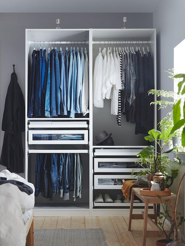 Eine offene PAX Kleiderschrankkombination mit Kleidung und Inneneinrichtungen wie Schubladen, Kleiderstangen und einem Hosenaufhänger.