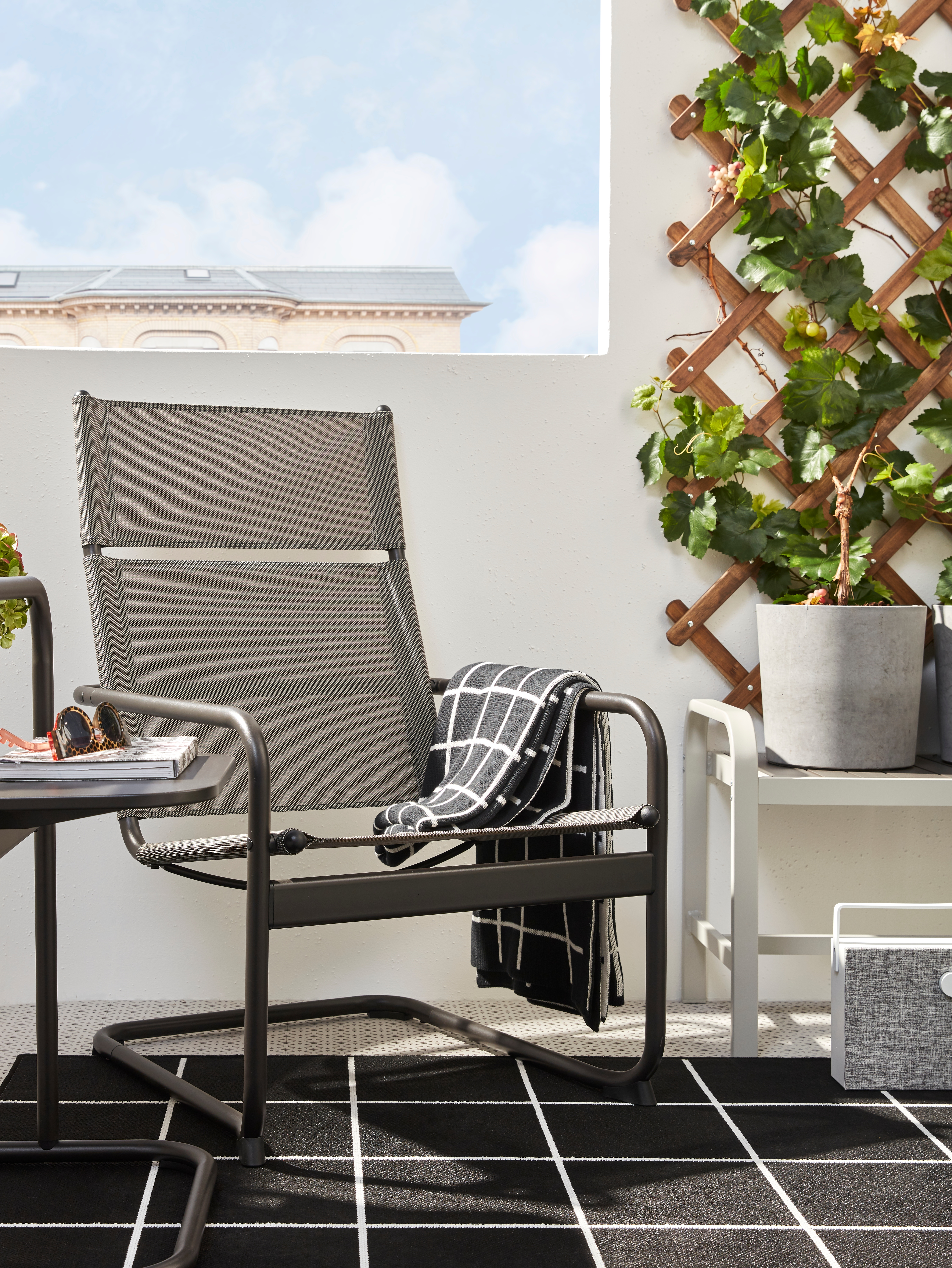A dark grey, outdoor HUSARÖ armchair is by a matching side table in a balcony corner with a rug and potted plants on a bench.
