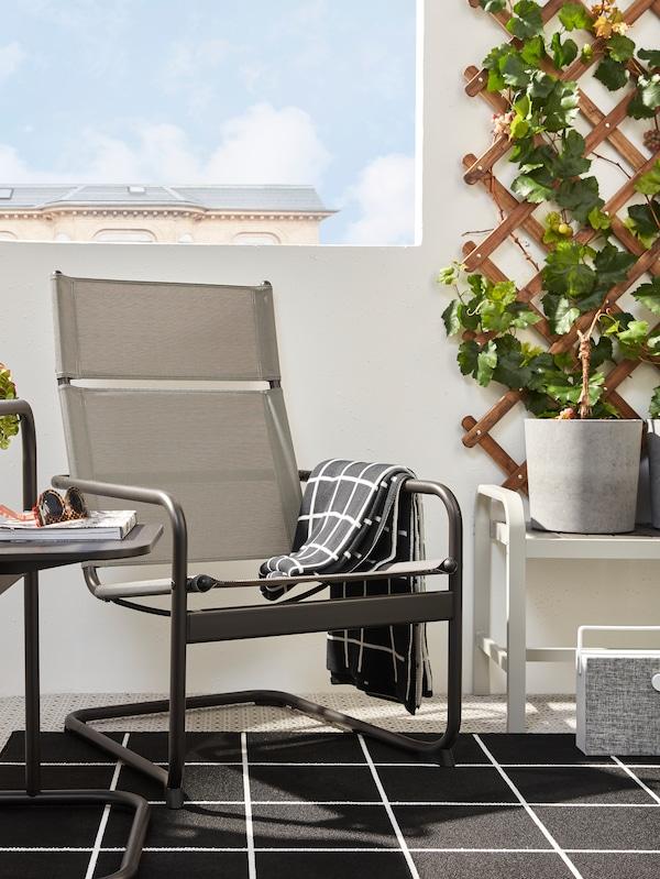 الكرسي بذراعينHUSARÖ والطاولةالجانبيةبلون رمادي داكن على سجادةفي شرفةبجوارمقعد مع آنية نباتاترمادي من أعلى.