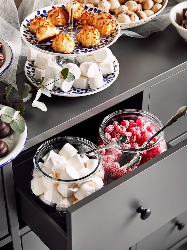 Detalle de una cómoda BRYGGJA gris con tarros de vidrio y platos llenos de dulces en la parte superior y el interior de un cajón.