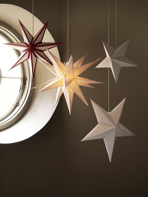 Four differently-sized STRÅLA winter stars hang in a small round window, with the one at the centre lit up inside.