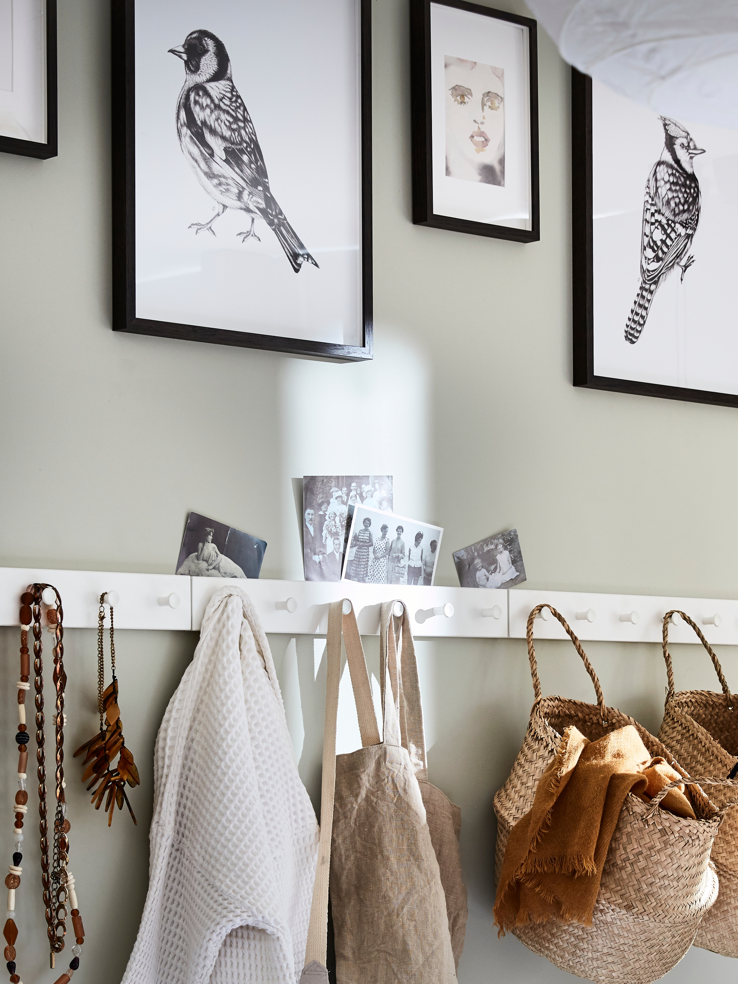 Tri bijele LURT/GUBBARP vješalice s okruglim kukama postavljene jedna do druge na zid s košarama i ogrlicama koje vise na njima.